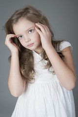 Portrait of a cute little girl straightens her hair..