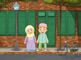 Muslim couple standing on the sidewalk