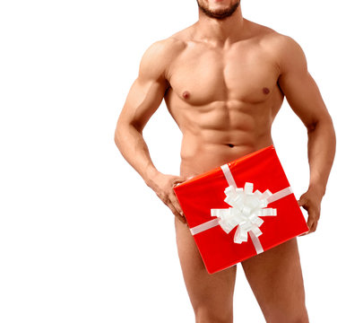 Special delivery. Naked man with stunning toned body posing with a present box isolated on white