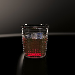Glass of whiskey with ice cubes on a dark background.