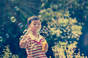 Asian child blowing soap bubbles, nature background. Vintage picture.