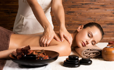 Beautiful woman having massage of body in spa