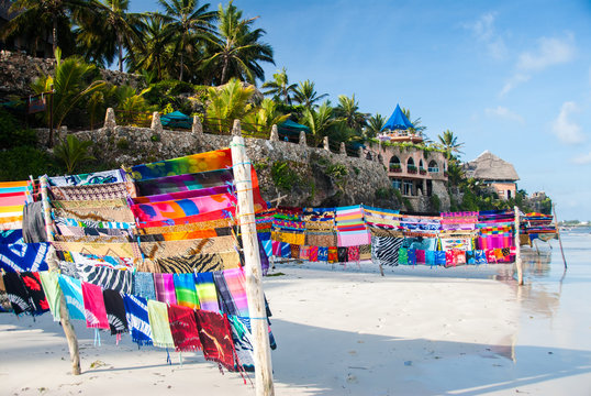 A collection of multicolored fabrics blowing in the breeze in an idyllic location