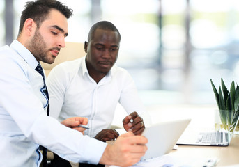Image of two young businessmen interacting at meeting in office