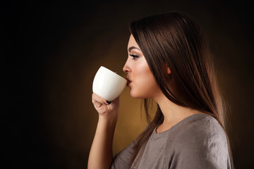 Portrait of pretty woman drinking coffee, close up