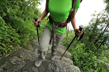 young woman backpacker hiking on mountain stairs..