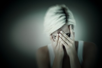 Composite image of sad blonde woman crying with head on hands