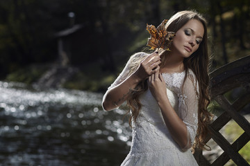 Girl model bride posing outdoors with leaves in their hands.