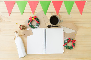 Christmas decoration with opened notebook and cup of coffee on wooden background