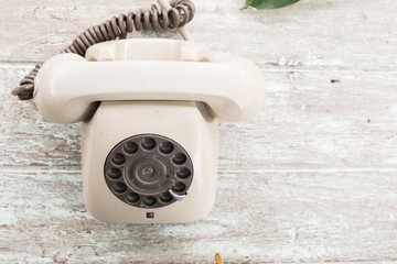 Retro telephone on wood table, top view