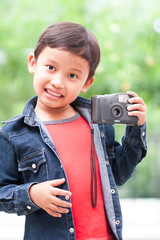 Happy asian boy with compact camera.