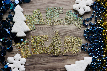 "Holiday decorations closeup on wooden background with holographic inscription ""New Year"""