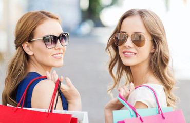 happy young women with shopping bags in city
