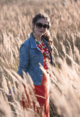 girl in sunglasses standing on the field in sun rays