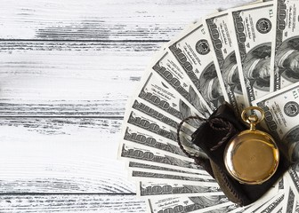 Stack of money dollars laid out like a fan with antique gold watch on white retro stylized wood background