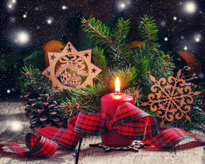 Christmas composition with burning red candles tied with plaid r