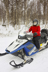 Woman driving a snowmobile in Ruka of Lapland