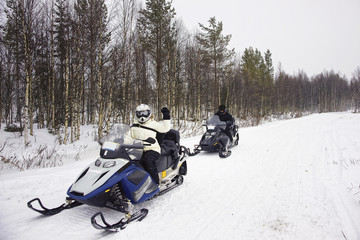 Woman and a Man driving snowmobile in Ruka of Lapland