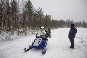 Woman driving snowmobile in Ruka in Lapland