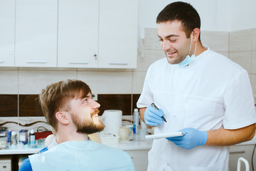 dentist taking notes with happy patient