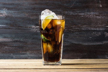 Glass of cola with ice and lime on the rustic background