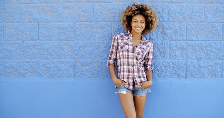 Female Posing Next To A Blue Wall