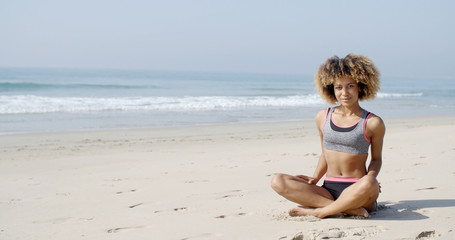 Woman Sitting On The Beach In Lotus Pose