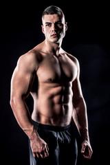 beautiful male athlete shirtless isolated over black background