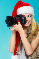 Photographer girl in santa claus hat shooting images