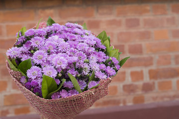 Bouquet of purple flowers in vintage brown brick as background with copy space