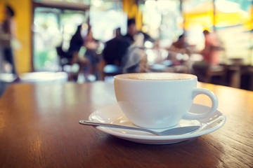Cup of coffee on table in cafe with people - shallow depth of field