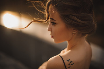 beautiful girl profile with tattoo on shoulder , soft focus