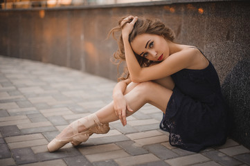 Ballet dancer in black dress and pointe shoes sitting on the ground