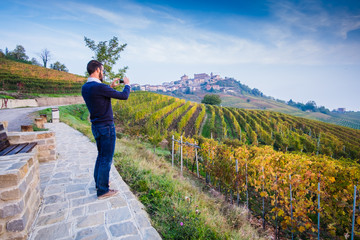 Man taking picture in a vineyard in autumn