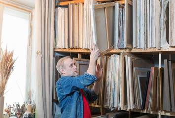 A male artist taking a painting from a shelf rack