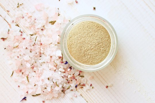 Cosmetic clay powder in jar and herbal aromatic salt. Healthy skin care.