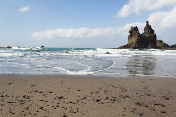 beach panorama with rocks in water, blue sky