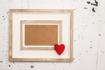 Photo frame with red heart over white vintage background