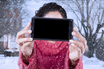 Woman shows cellphone with empty screen at wintertime