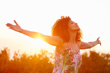 Woman outstretched arms in an expression of freedom with sunflar Wall mural