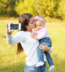 Happy mother and baby taking self-portrait on smartphone in sunn