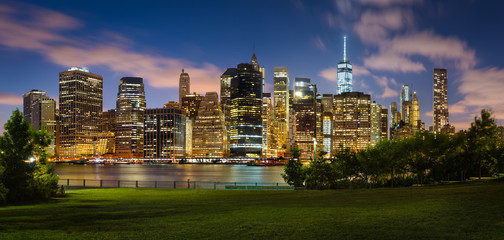 Wall Mural - Lower Manhattan skyline and green lawn of Brooklyn Bridge Park at twilight.Illuminated skyscrapers of the Financial District reflect on the East River. New York City.