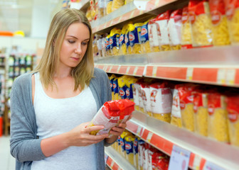 Woman choosing pasta in grocery store.
