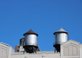 Water Tanks on Building Roof with Blue Sky Background