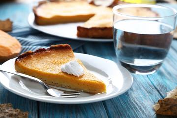Tasty pumpkin pie on plate on a blue wooden table