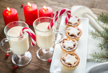 Two glasses of eggnog with mince pies