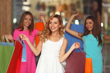 Beautiful young women with bags in shopping center