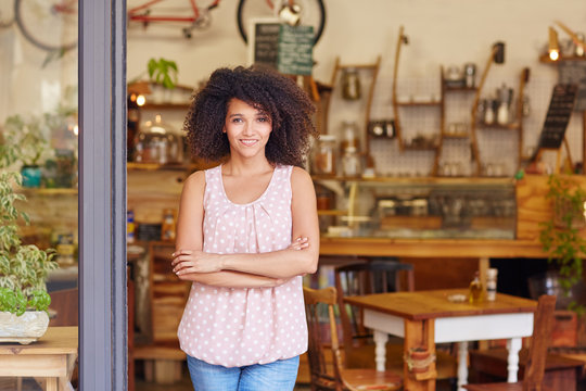 Small business owner standing proudly in the door of her coffee