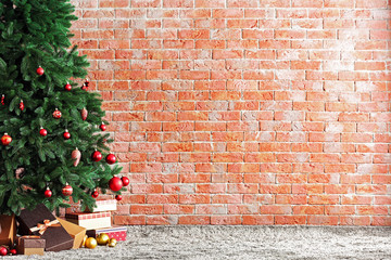 Christmas tree with presents in a room on brick wall background