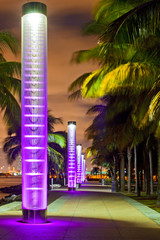 Miami BEach Florida at night, South Pointe park colorful lights and pedestrian path by the ocean and panorama of downtown in the background. Famous tourist destination.